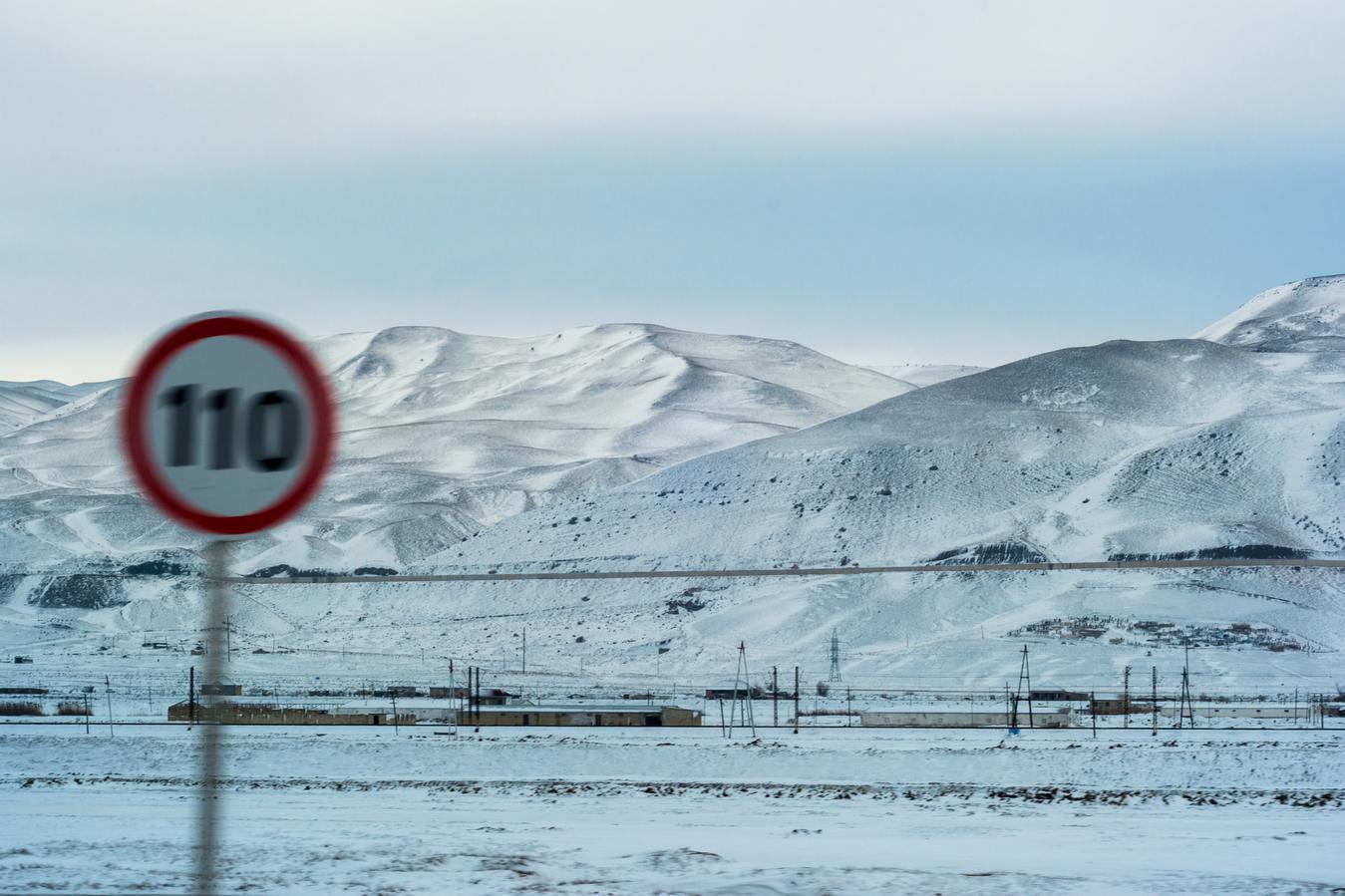 Paesaggio innevato con segnale di limite di velocità sfocato
