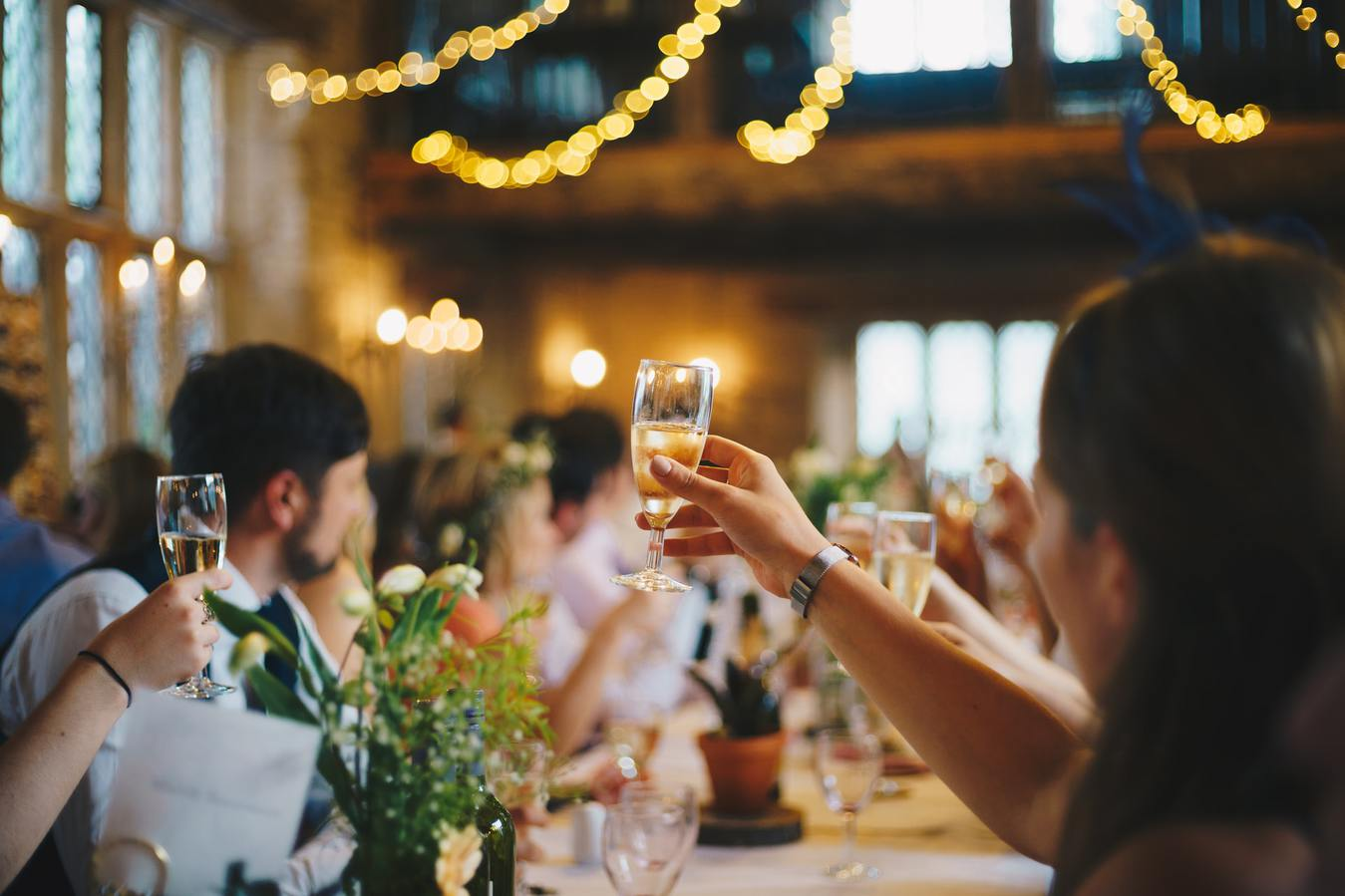 People cheering and raising a glass at a wedding