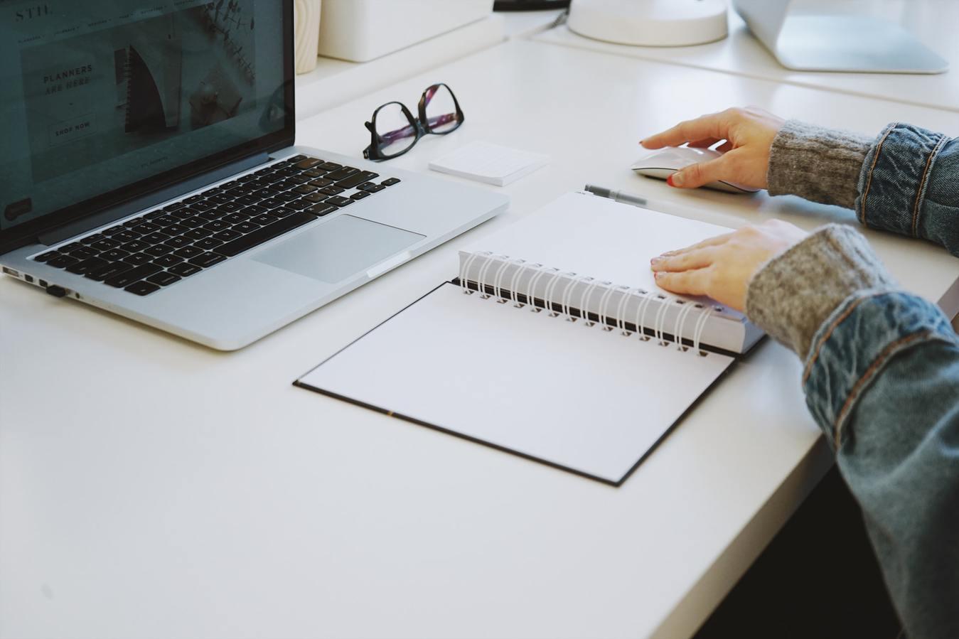 Osoba siedząca przy biurku, laptop i notes.