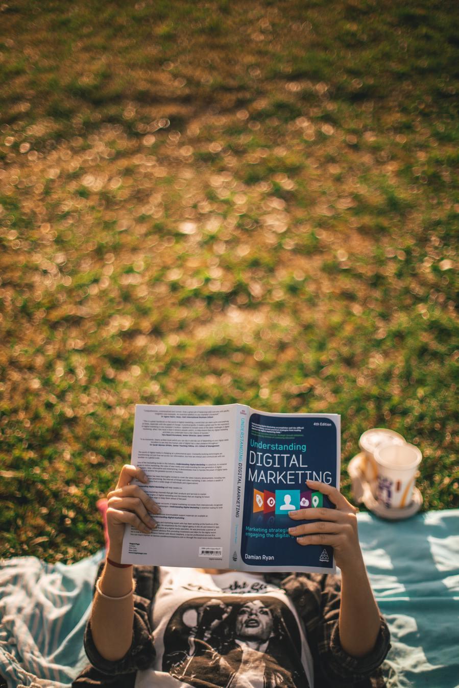 Persoon die buiten een boek over digitale marketing bestudeert