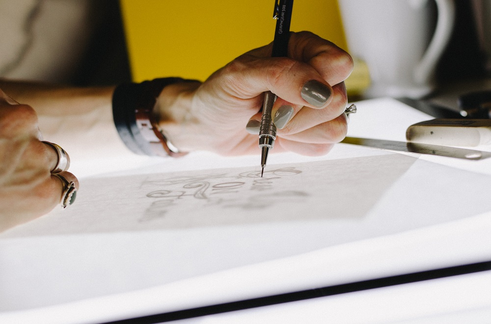 persoon tekent ontwerpen op lichtbox