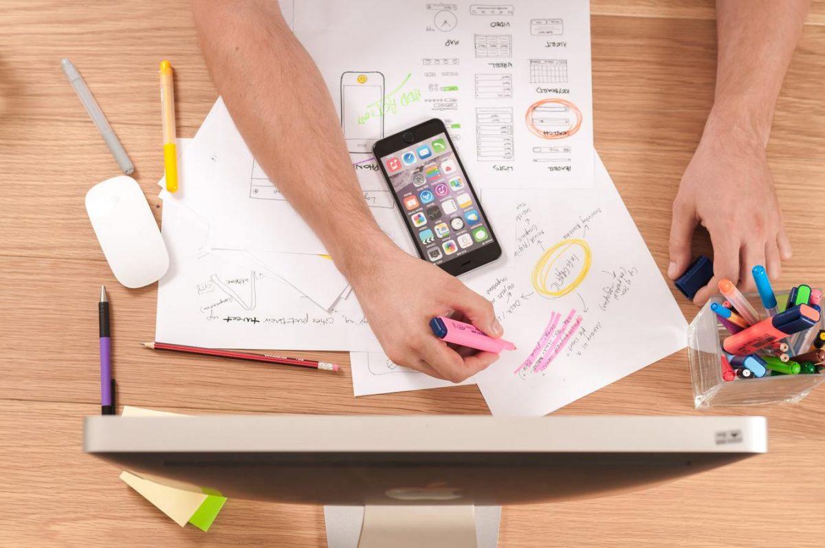 Pessoa no seu espaço de trabalho com papéis e computador