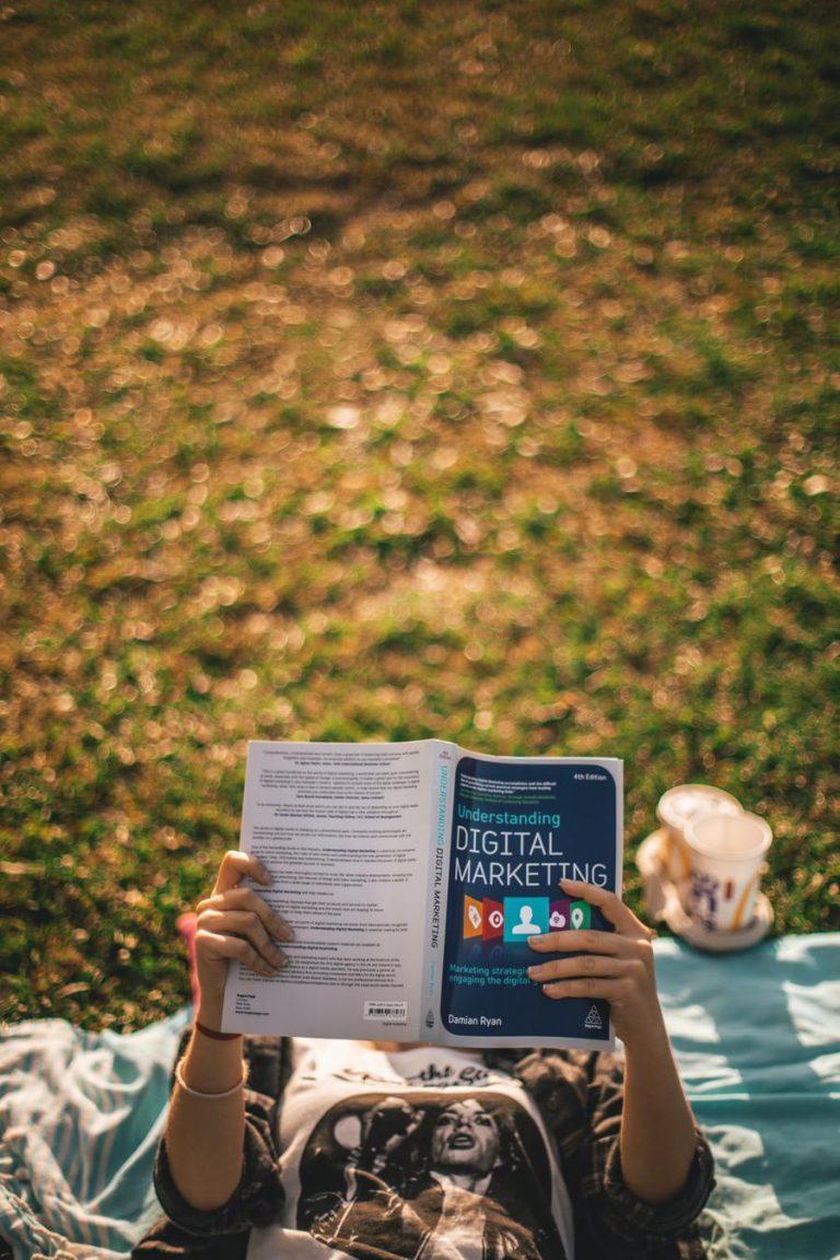 Pessoa a estudar um livro de digital marketing no parque