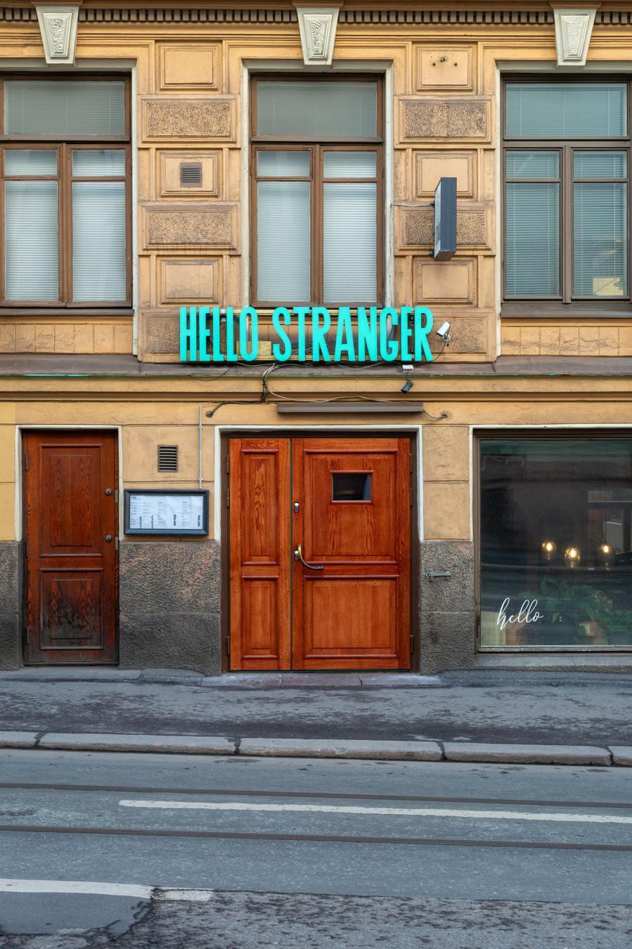 """Placa """"hello stranger"""" em um prédio"""