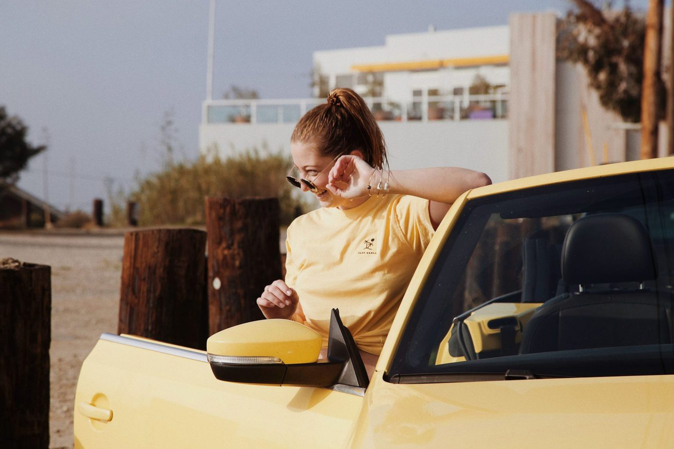 A woman in a car wearing sunglasses