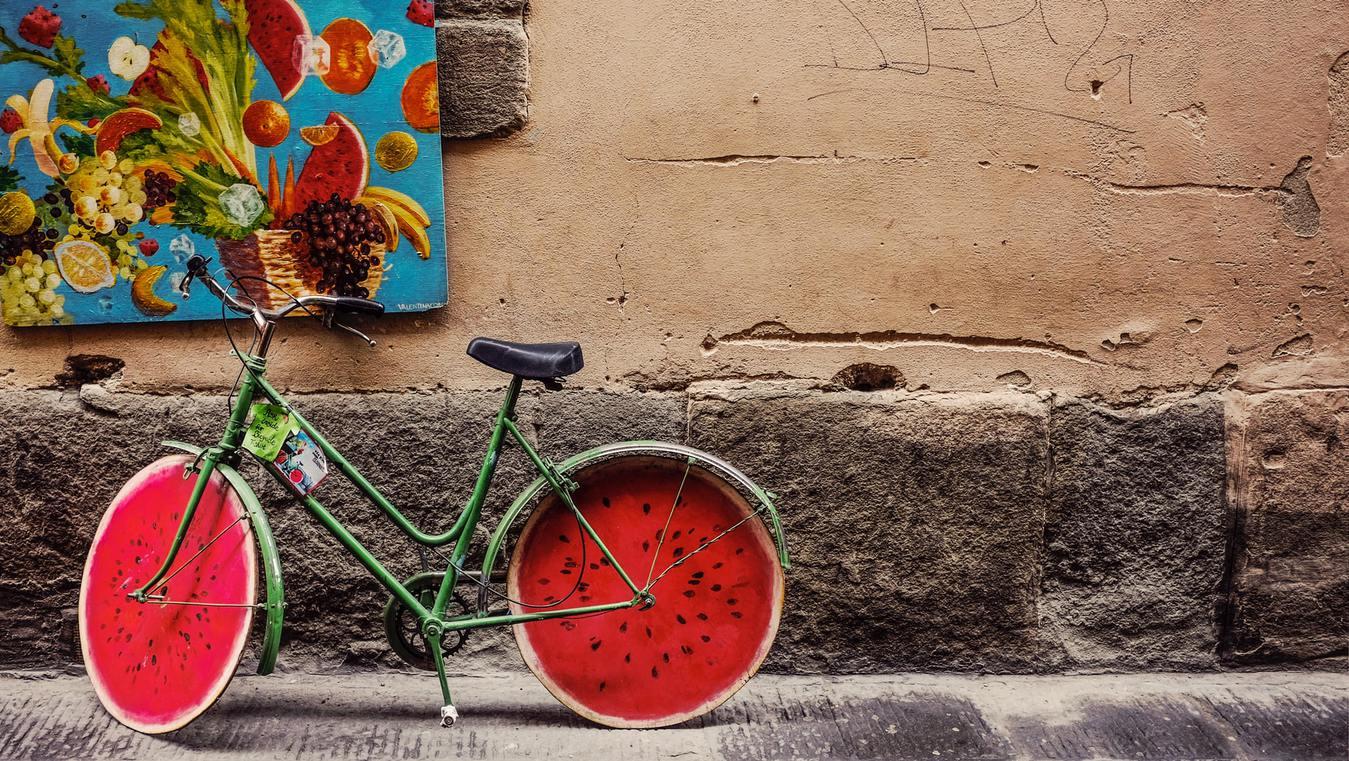 Bicicleta pintada como uma melancia parada na rua