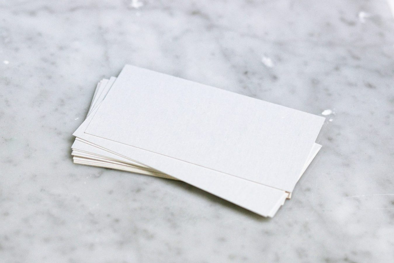 A pile of blank business cards on a marble table