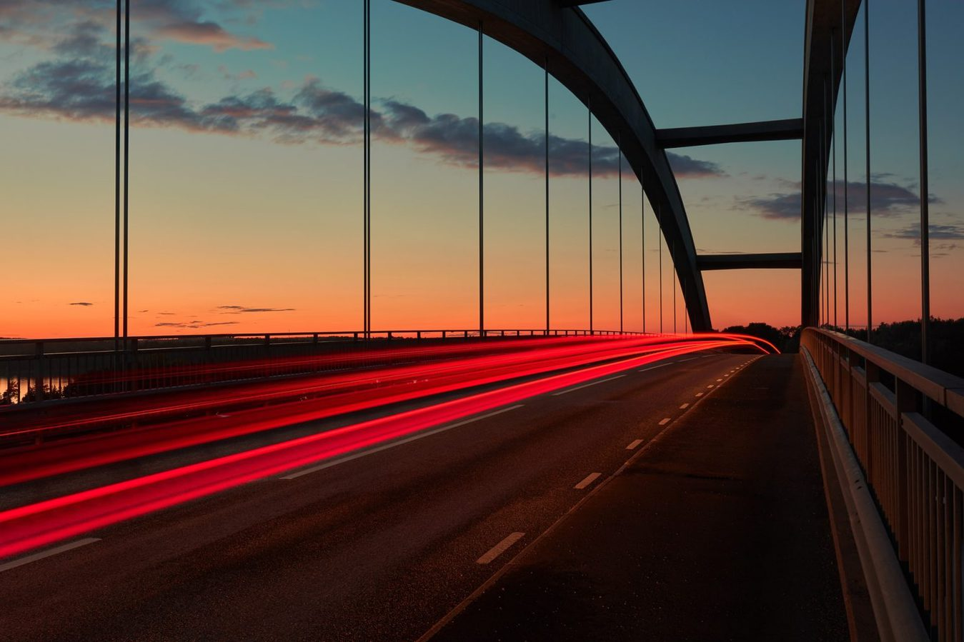 Blurred car lights on a bridge at sunset