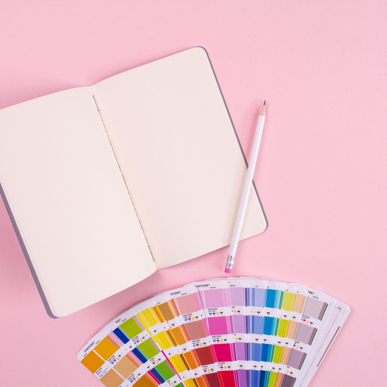 Color swaps and a journal with a pen against a pink background
