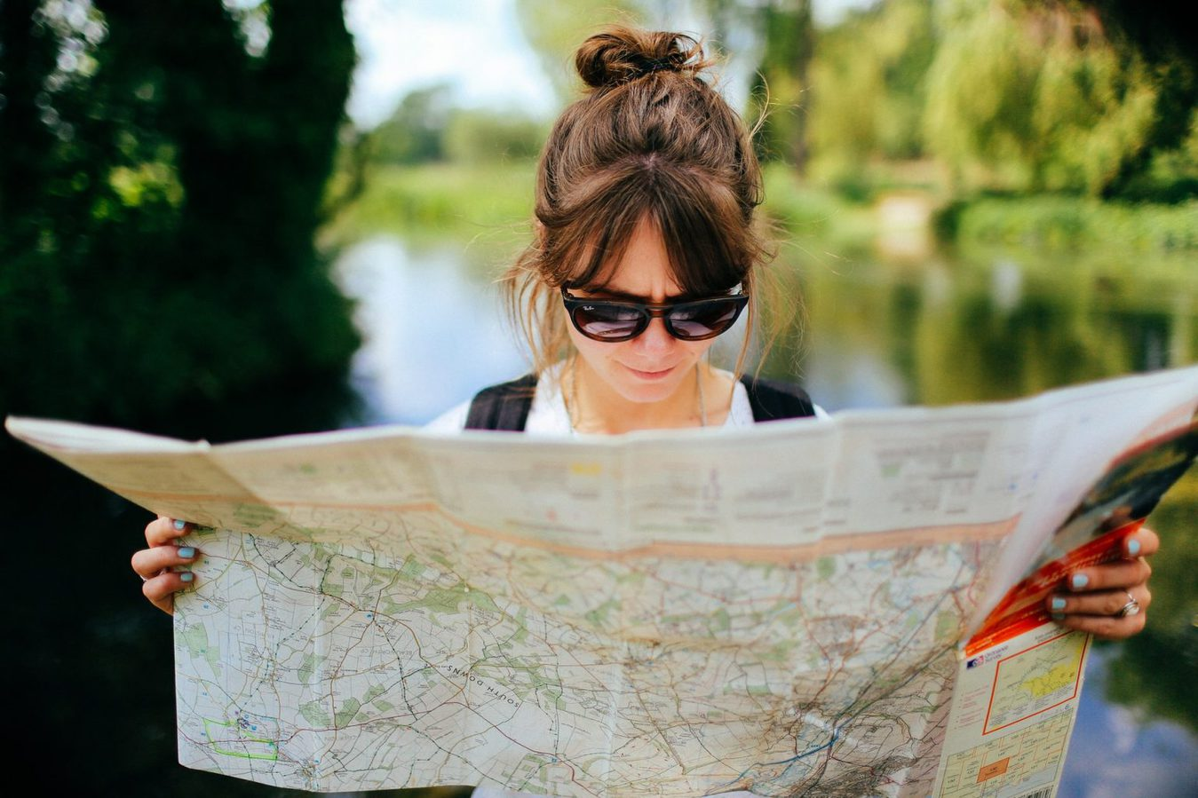 A girl reading a map outside