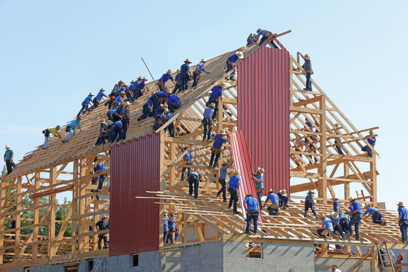 Group of people building a house outside