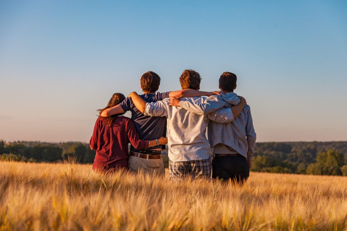 A group of friends in a field against a blue sky