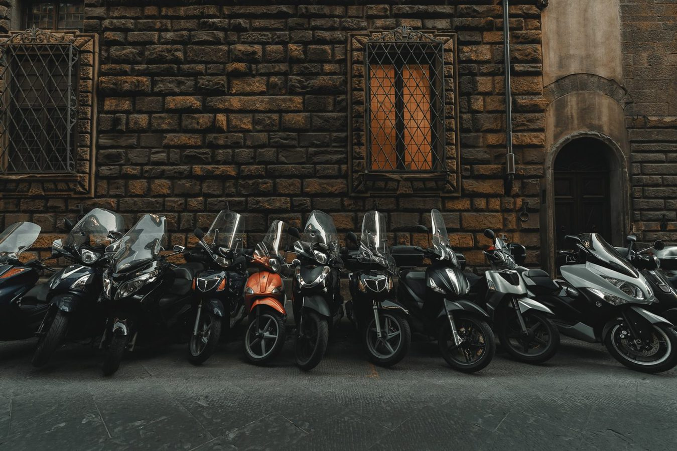 Mopeds standing at a brick wall