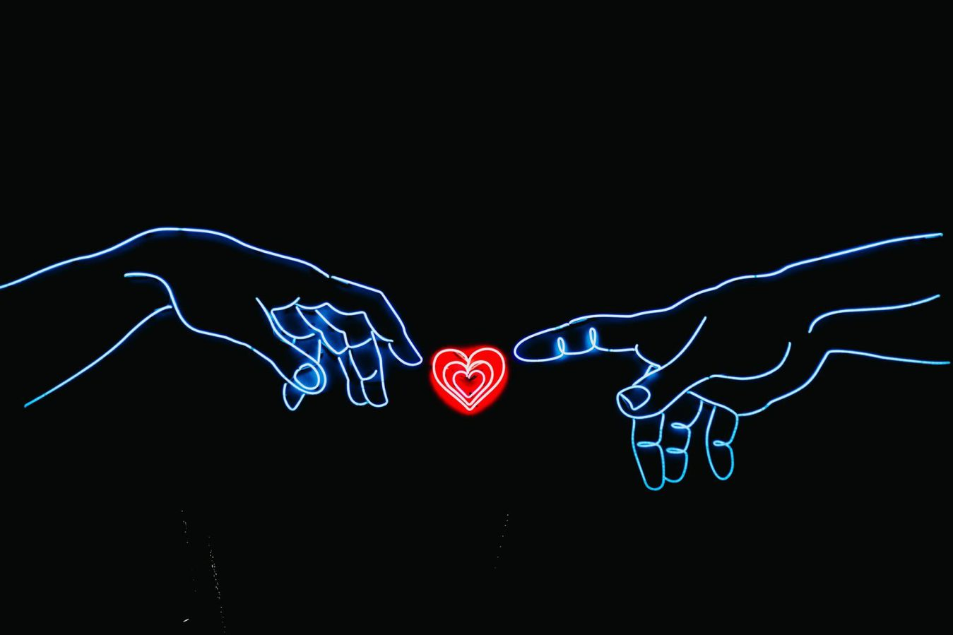 Neon sign two hands and heart