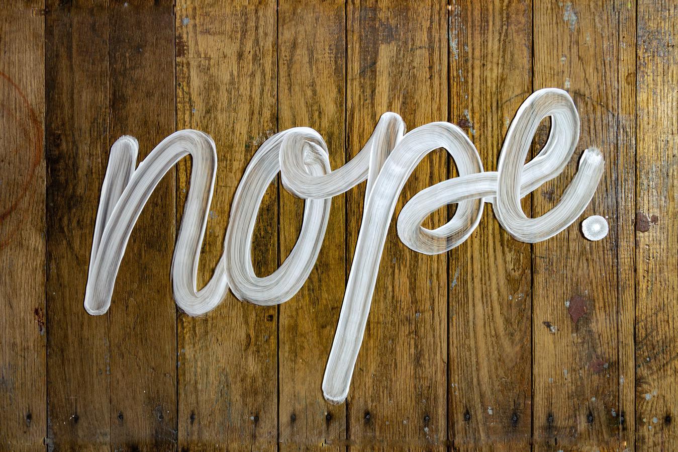 Palavra nope escrita sobre fundo de madeira