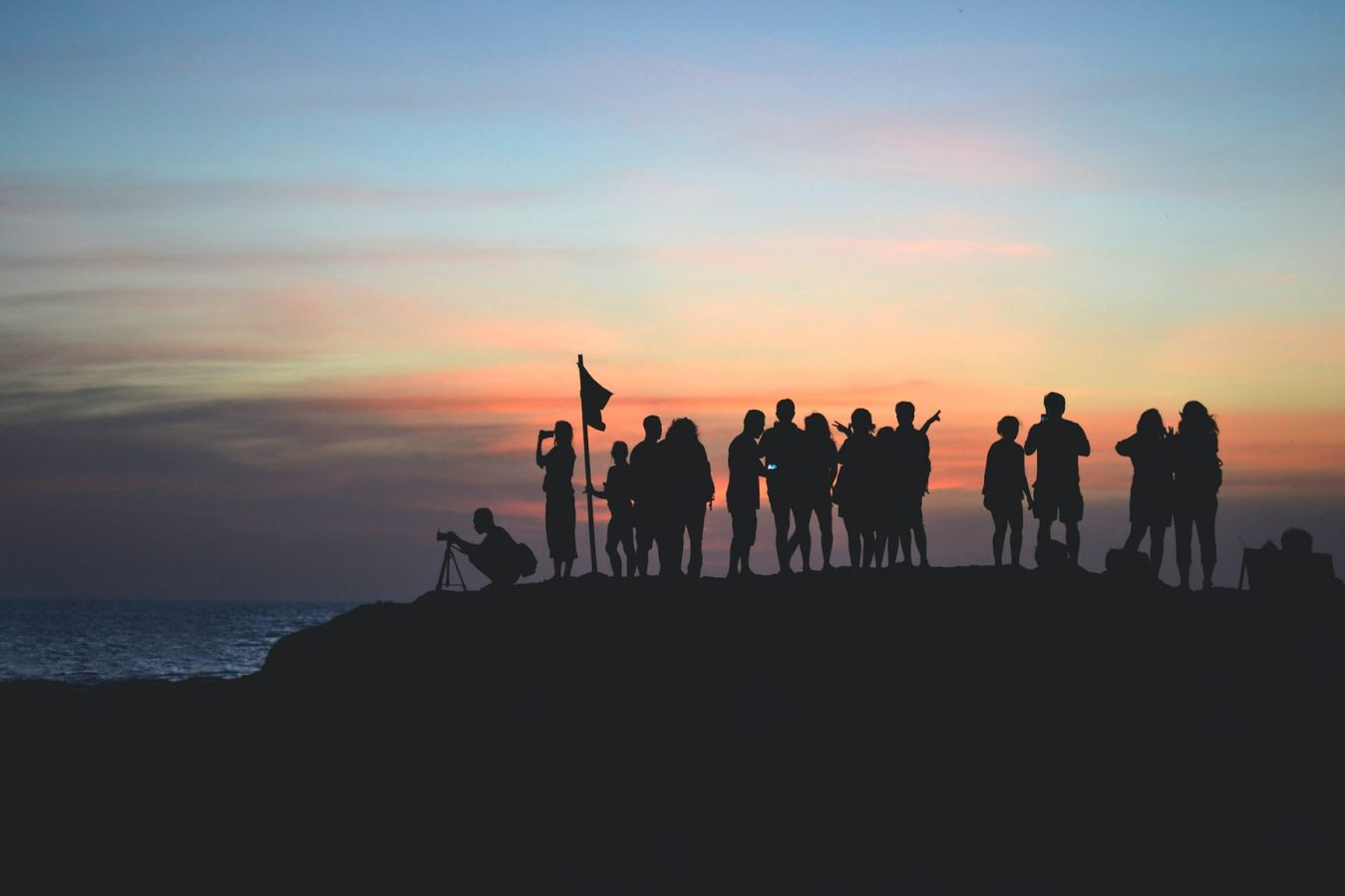 Group of people together at a cliff side at sunrise