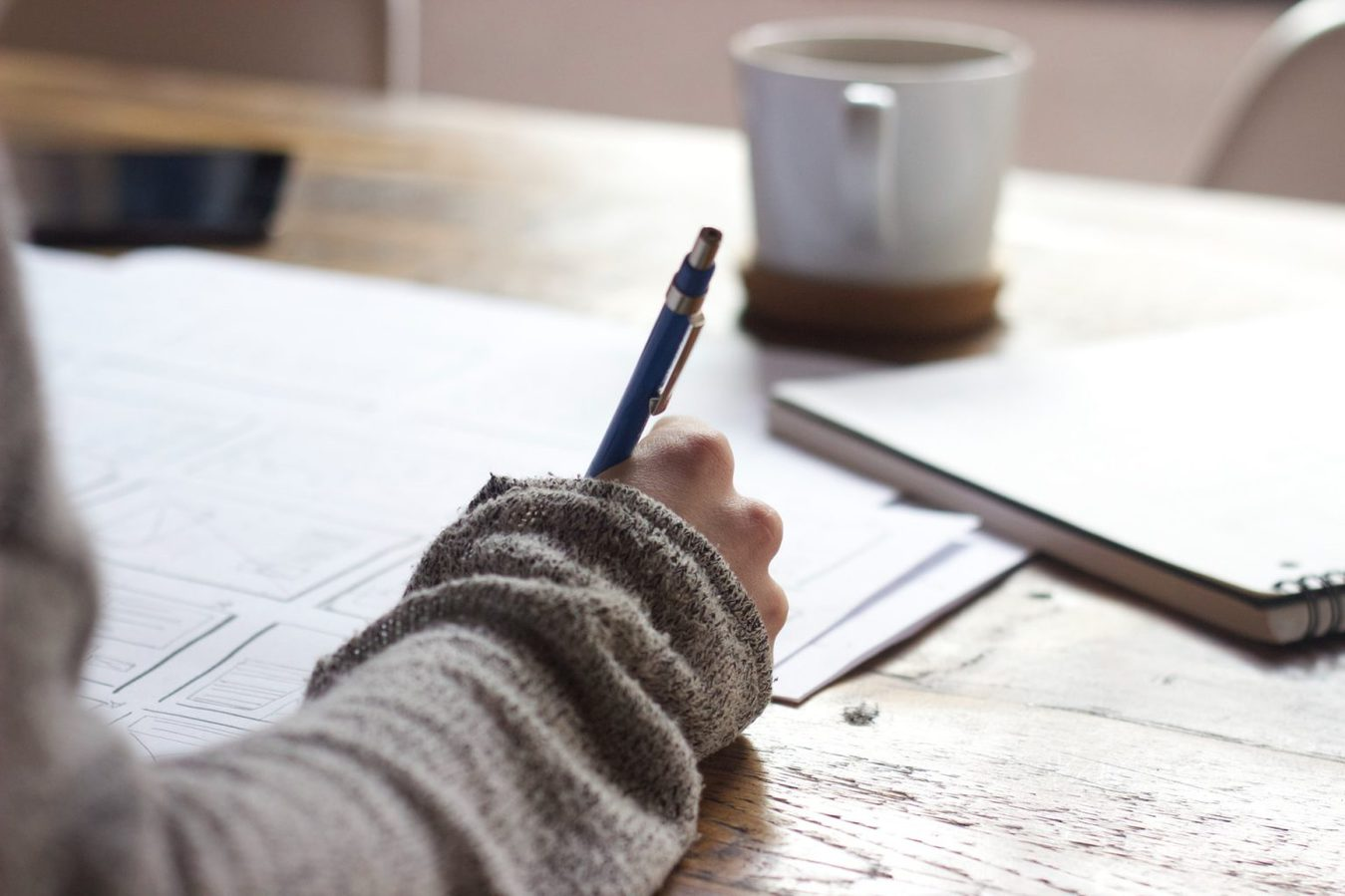Person writing in a journal on a table