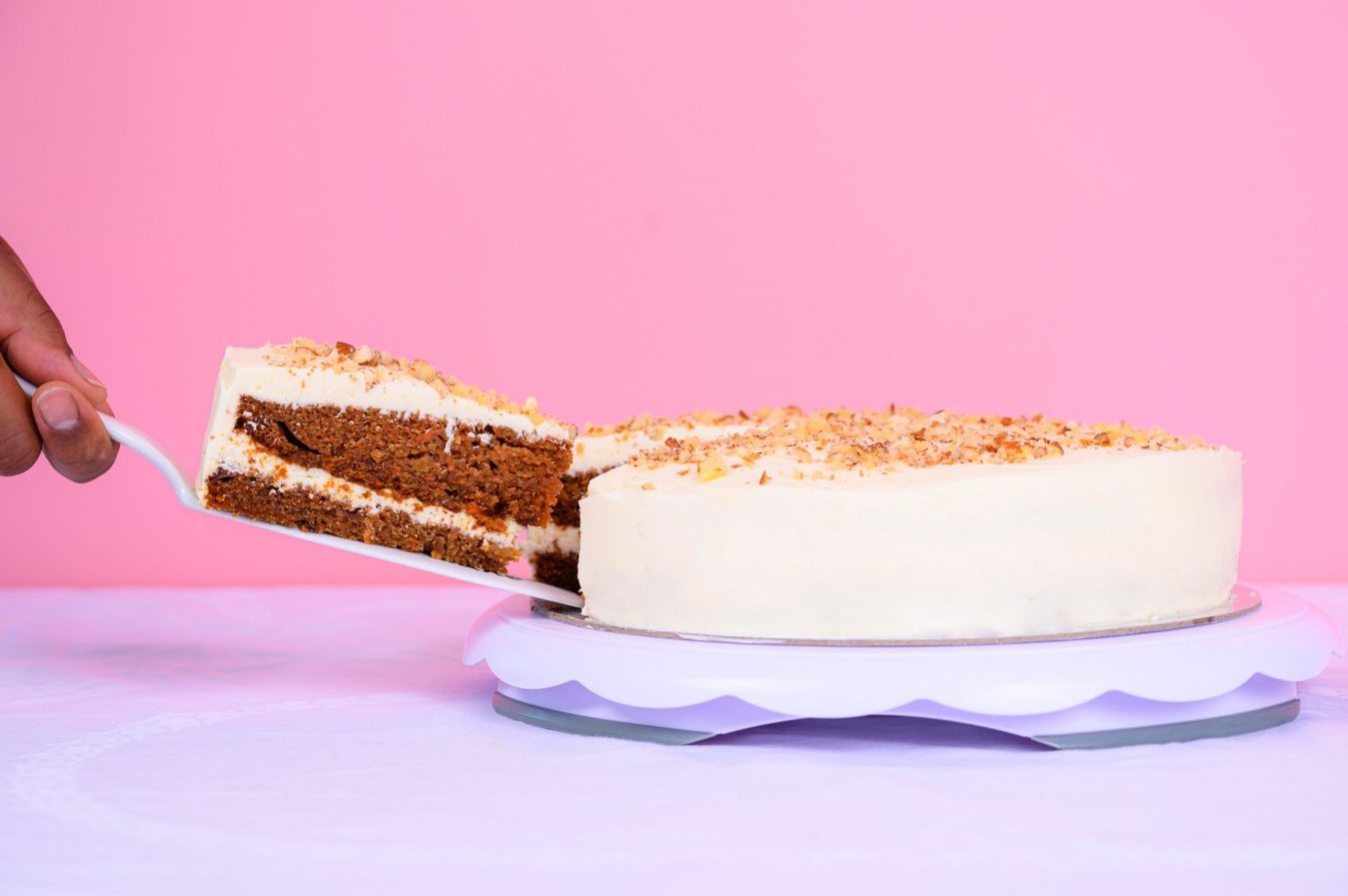 White cake on a table against a pink background