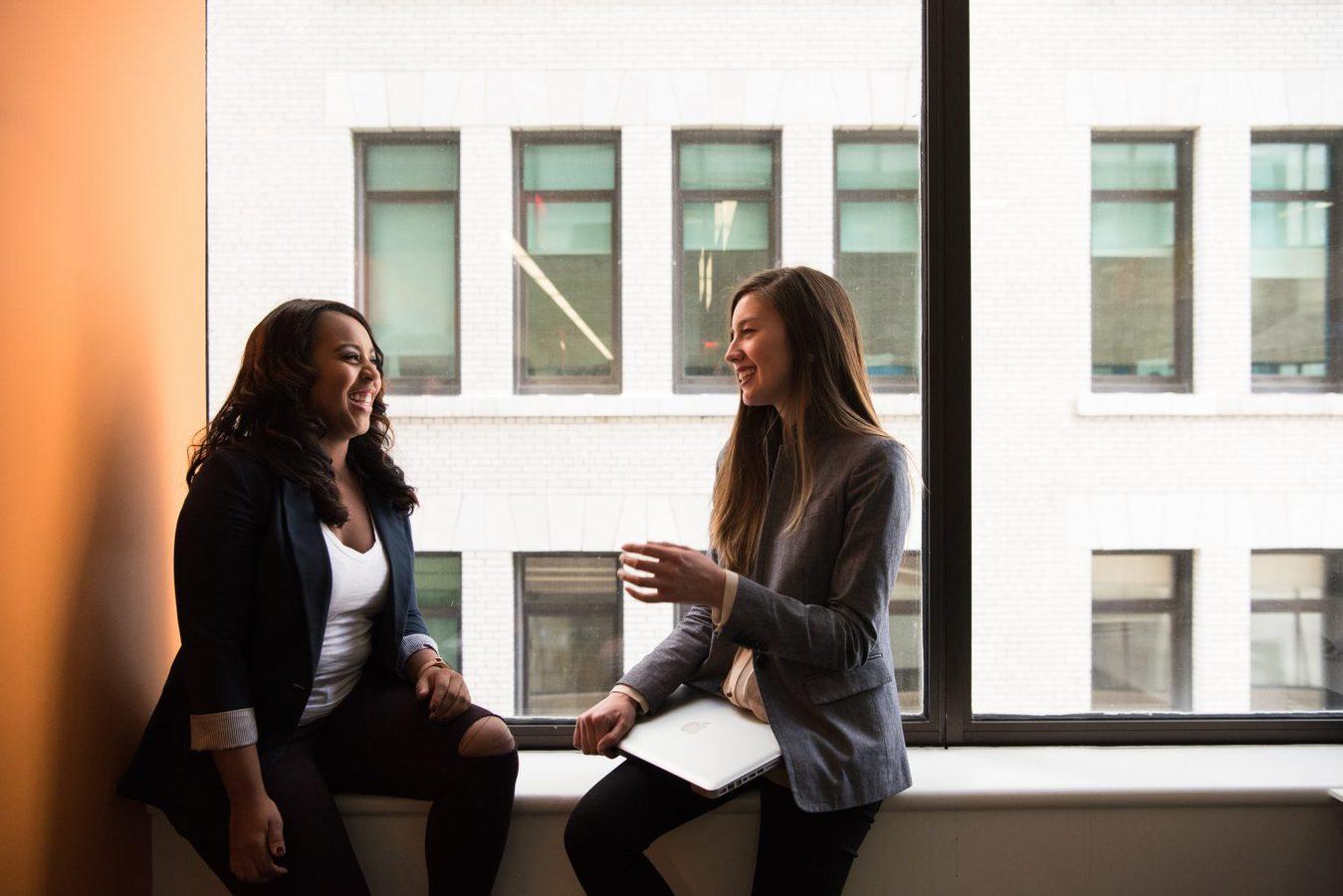 Women having a conversation next to a window