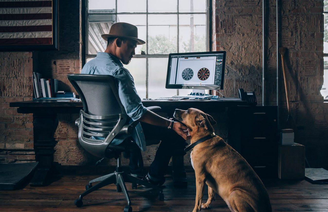Homem a trabalhar no PC e a afagar o cão