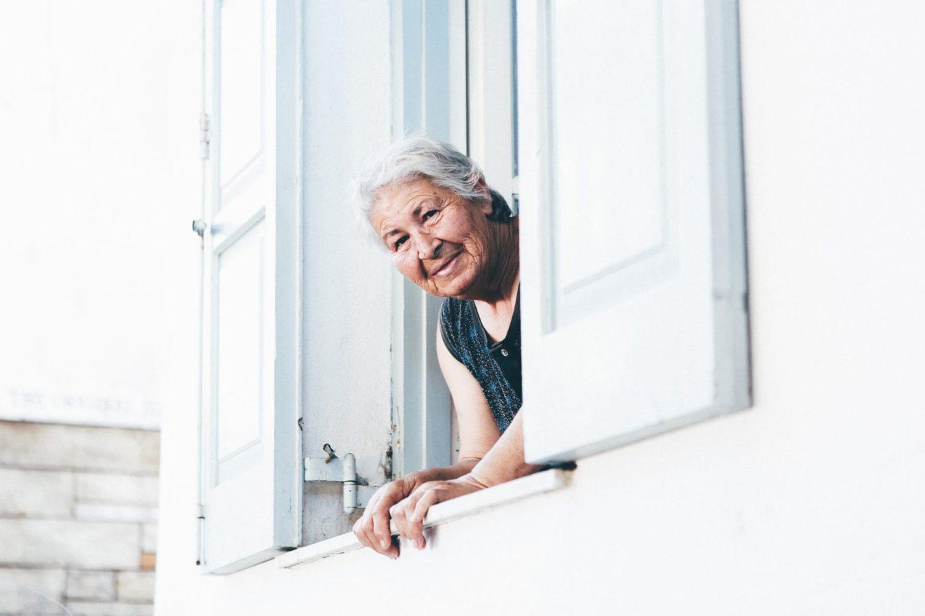 Oudere vrouw kijkt door raam