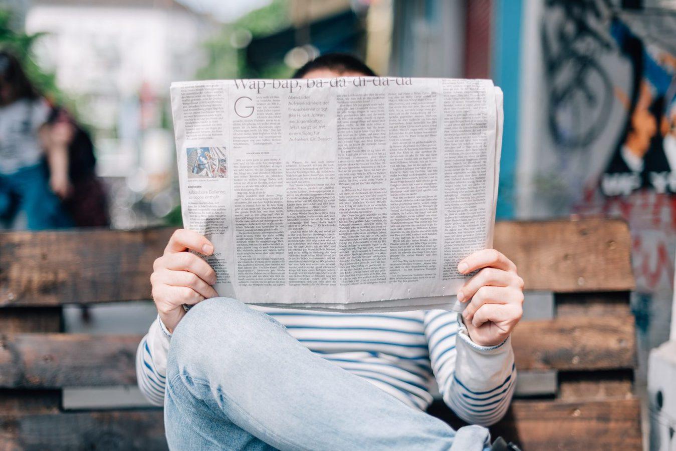 Een persoon die buiten op een bankje een krant leest