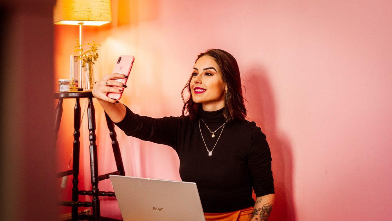 Een persoon die een selfie maakt tegen een roze muur