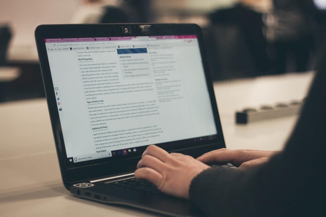 Persoon die een blog schrijft op een laptop