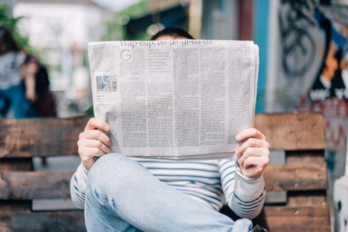 Seseorang membaca koran di bangku
