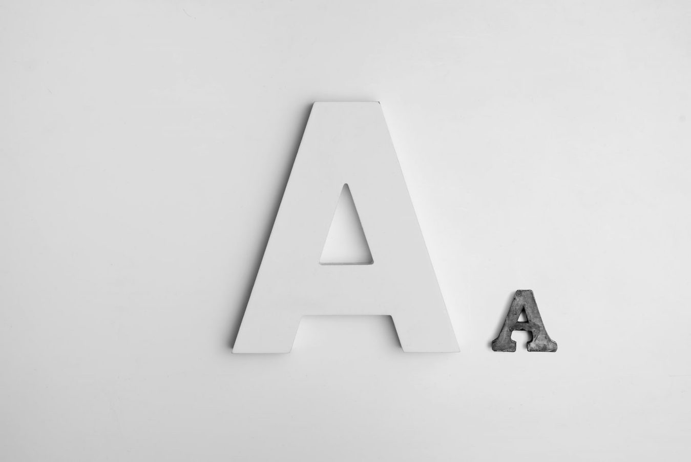A white and a black letter against a white background