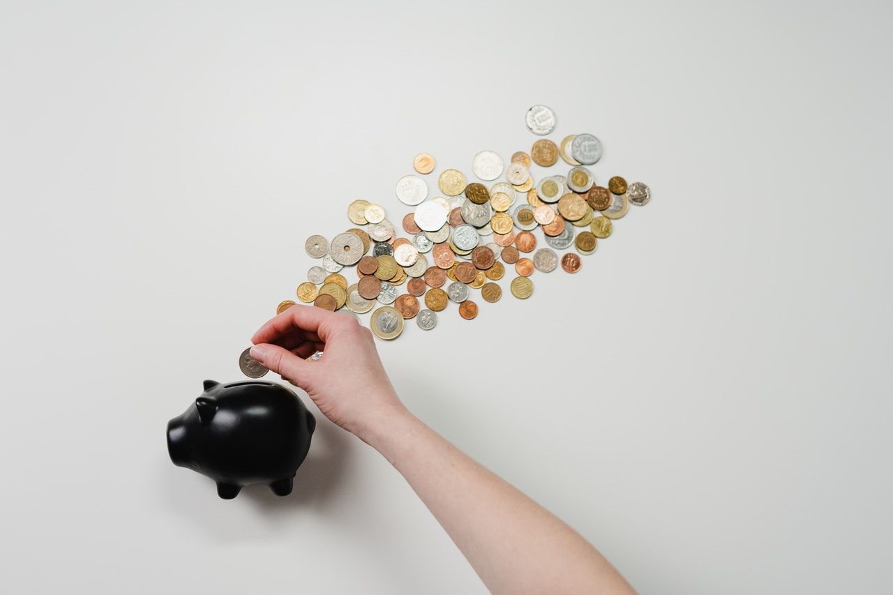 A black piggy bank with a cloud of coins above with against a white background, with a hand putting more coins into the piggybank