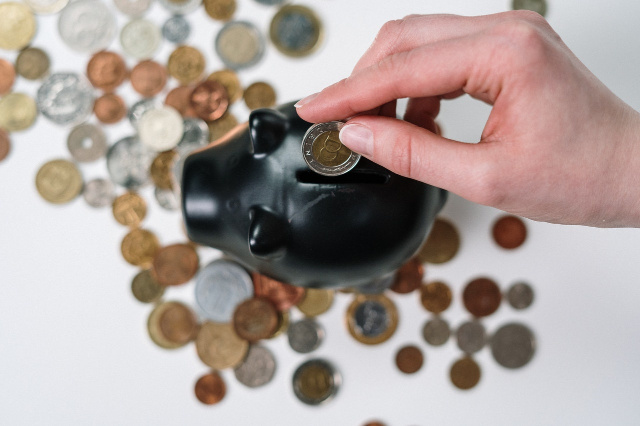 A black piggybank being filled with more coins, viewed from above