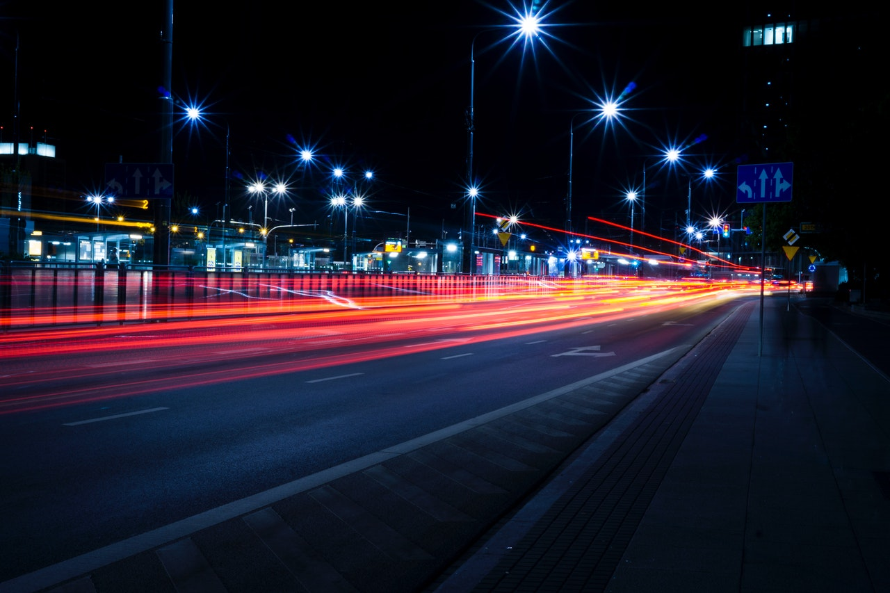 A night view of a city with cars speeding past