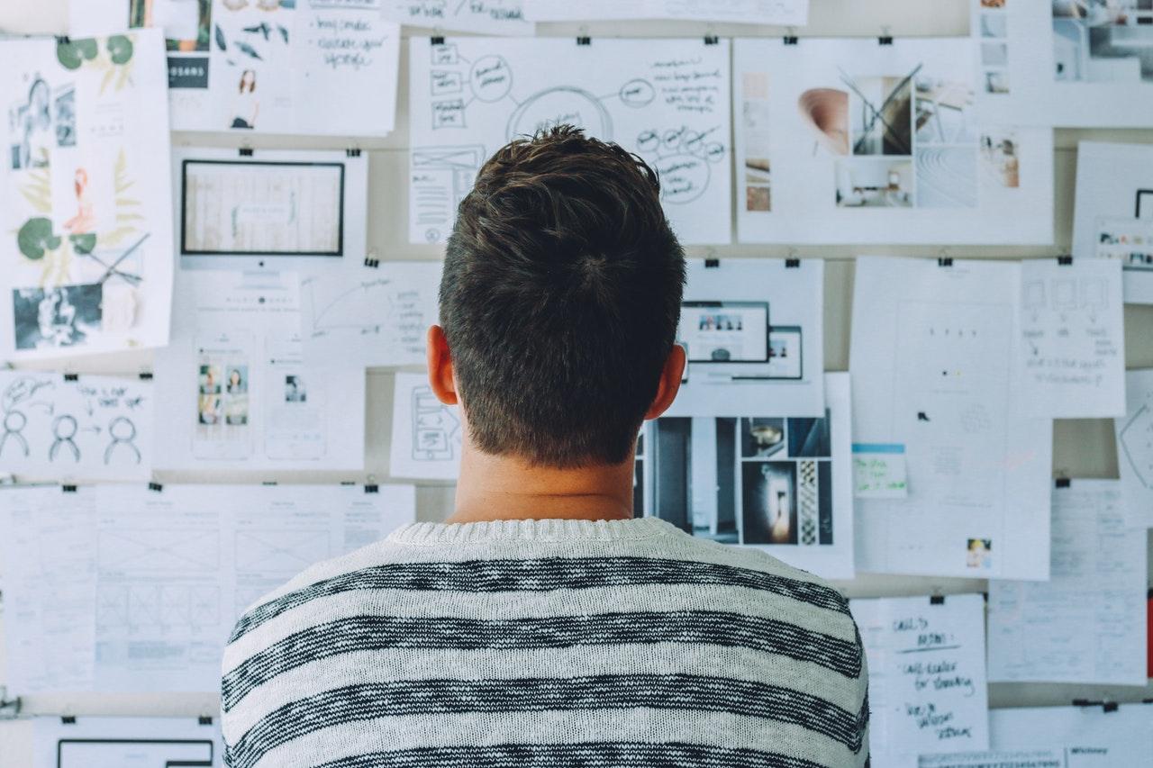 Człowiek wpatrujący się w ścianę, na której znajdują się różne notatki