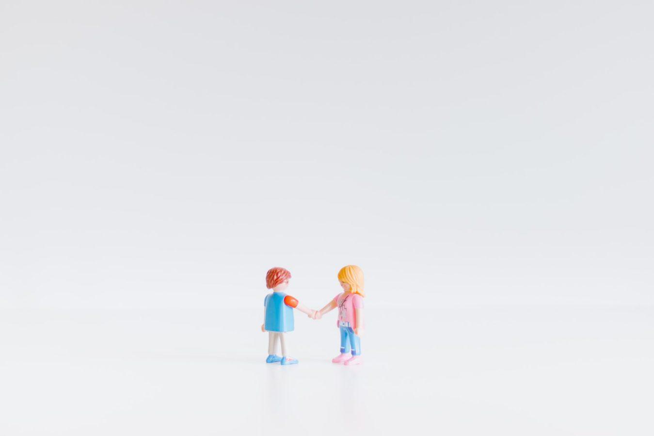 Twee speelgoedfiguurtjes die handen schudden