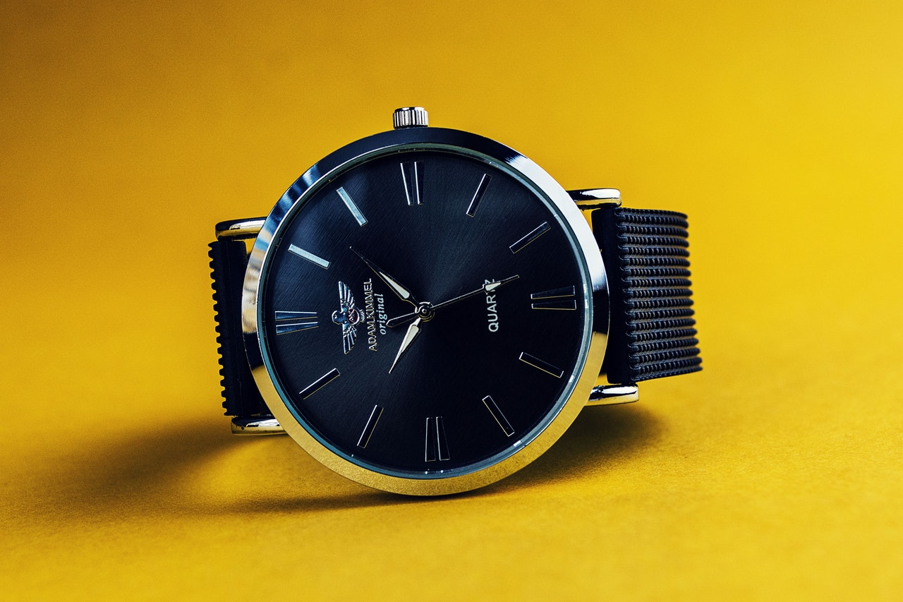 A watch photographed under studio lights against a yellow background
