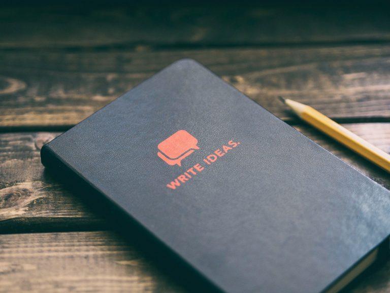 Caderno de ideias em cima de mesa de madeira