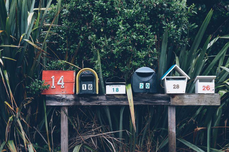 Caixas de correiro perto de arbusto