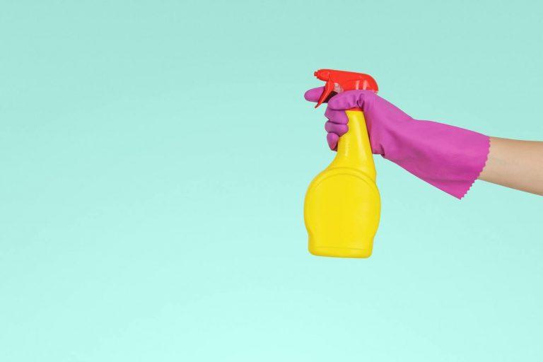 Uma pessoa segurando uma garrafa spray amarela com fundo azul