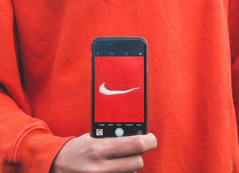 Logo da Nike em tela de celular, camisa vermelha ao fundo