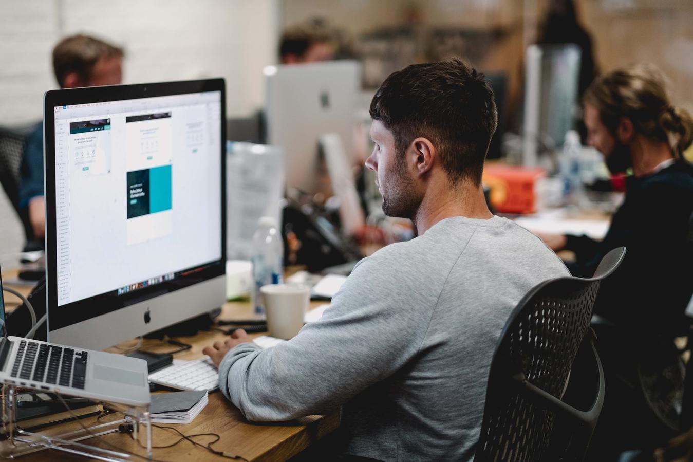 Man ontwerper werkt met desktopcomputer