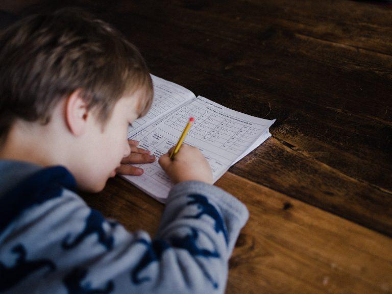 Um menino estudando na mesa de madeira