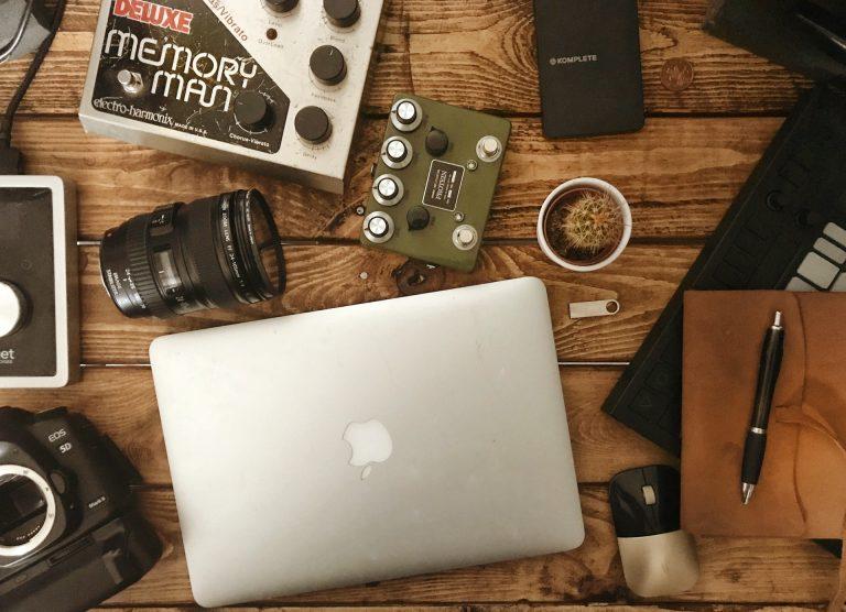 Notebook no meio de uma mesa bagunçada