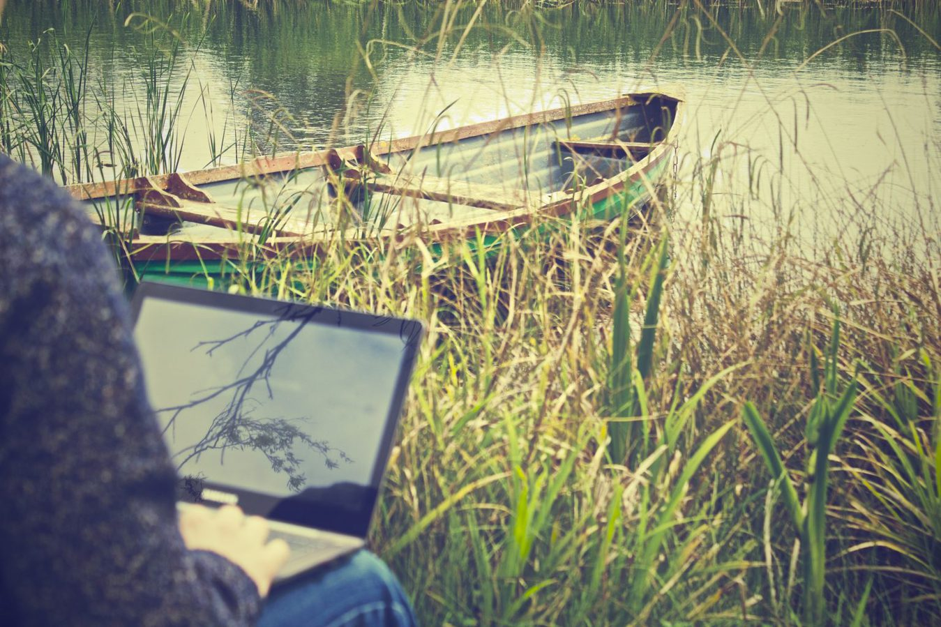 person sitting by a lake typing on a laptop