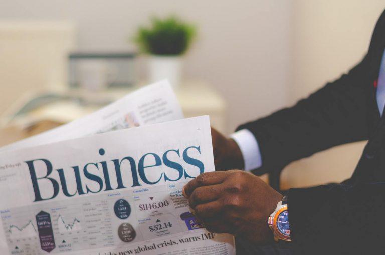Pessoa de terno lendo jornal sobre negócios