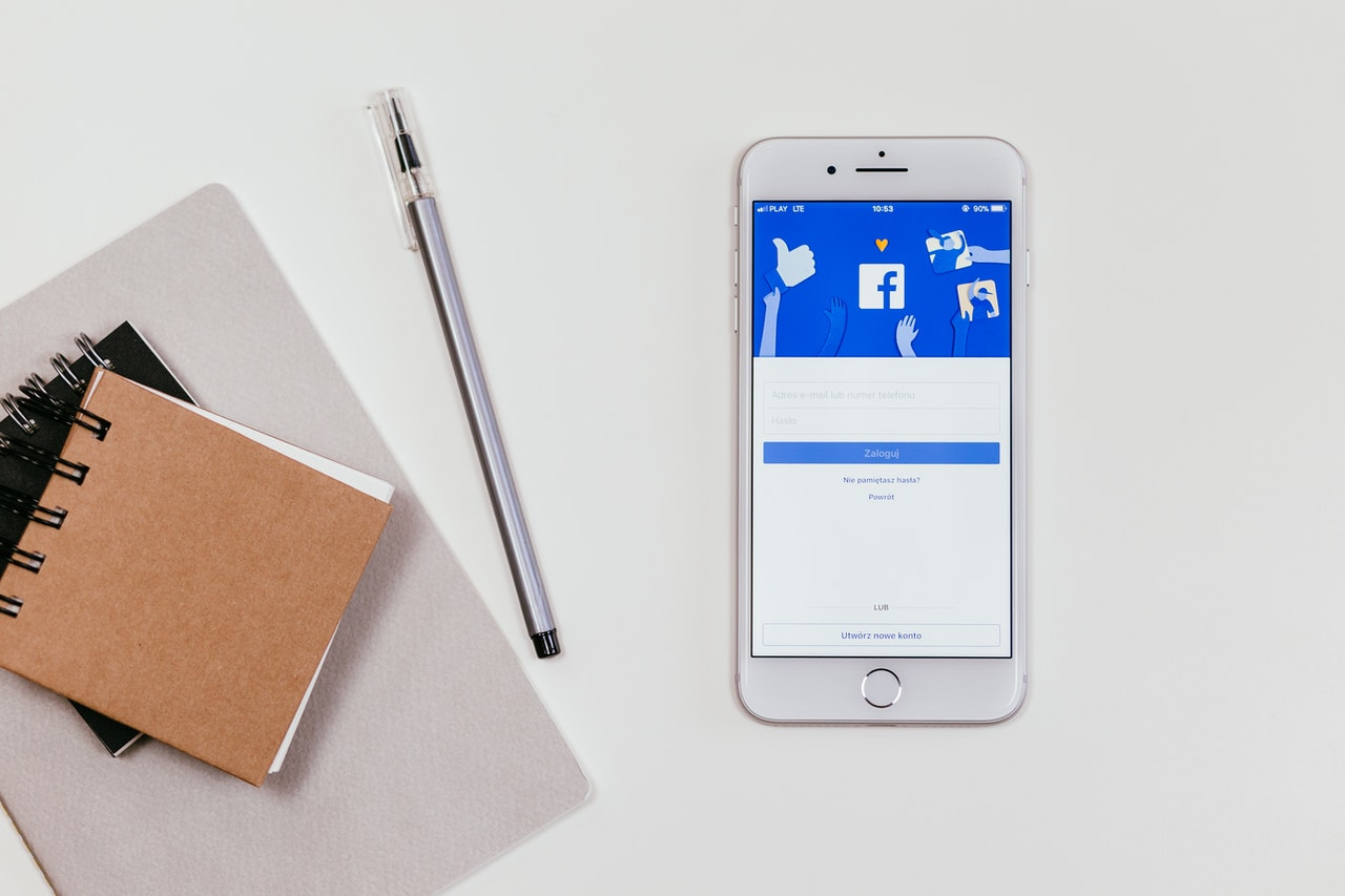 Facebook open on a mobile phone with pens and stationery on a white table