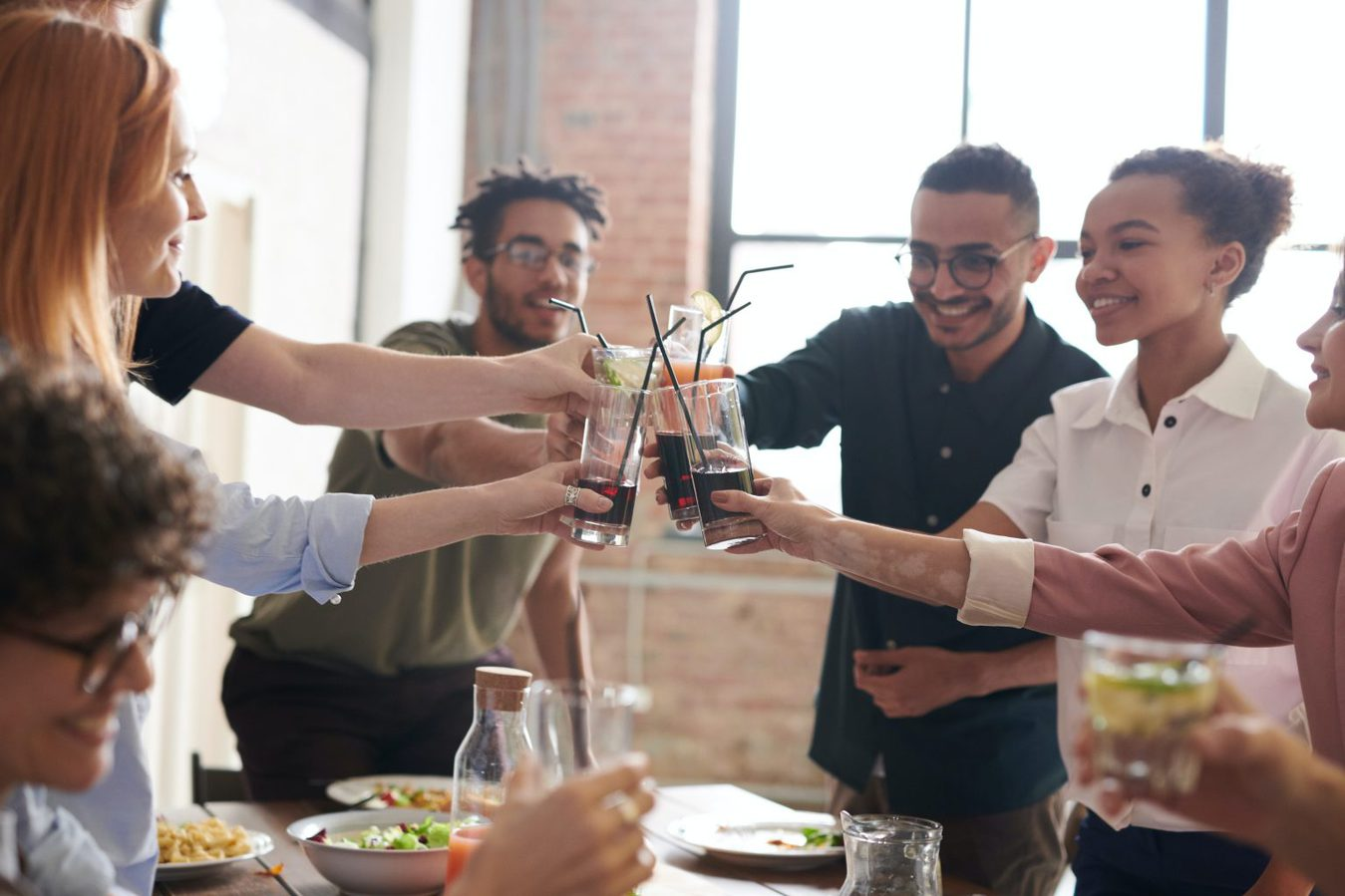 group of people making a toast with drinks over a table