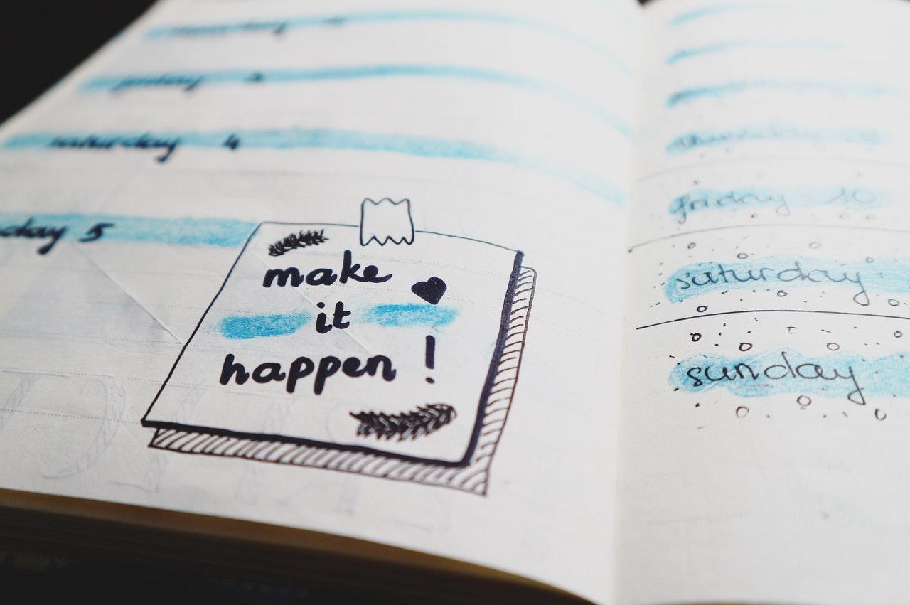 Een kalender met een post-it-notitie die zegt: make it happen