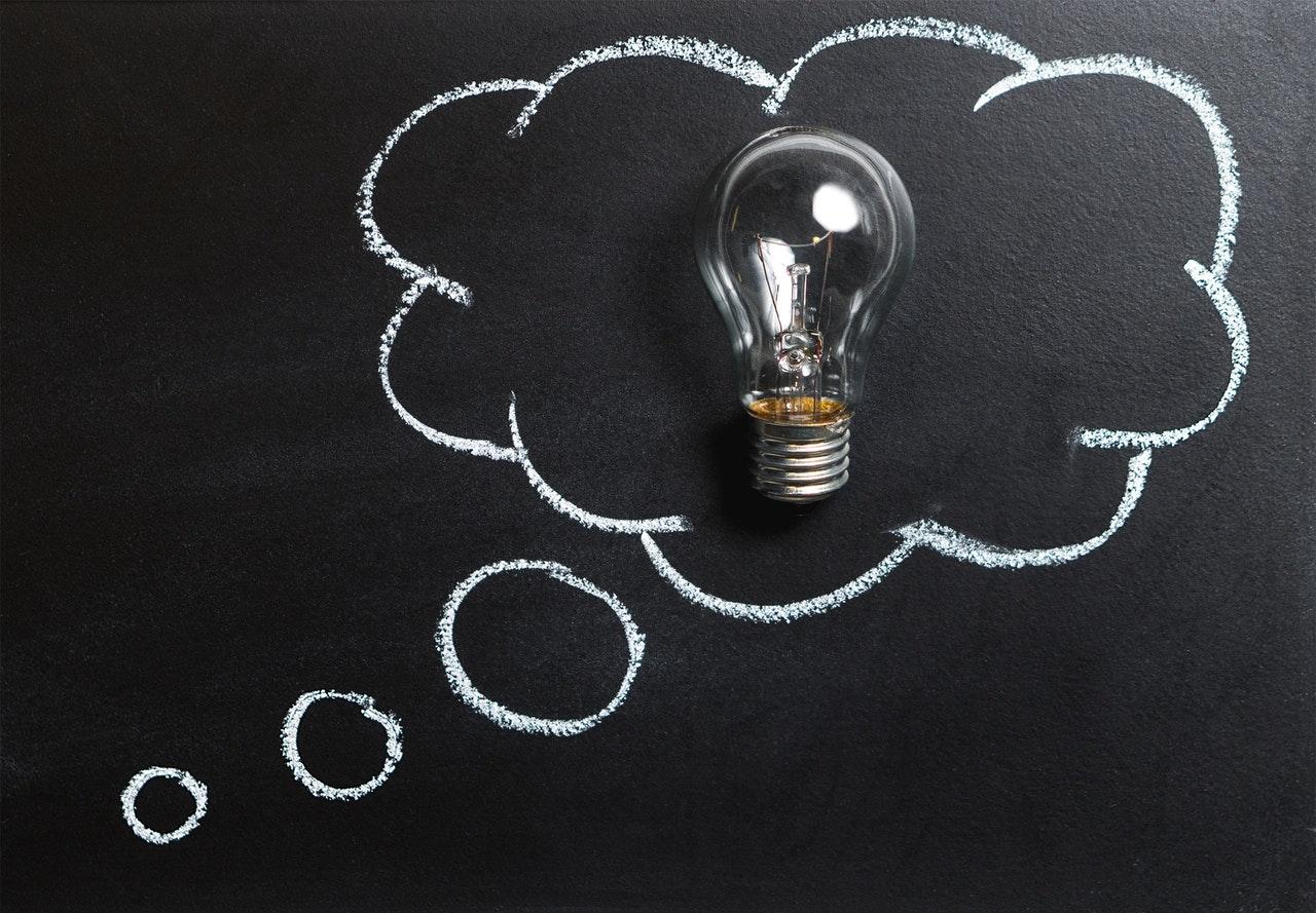 Een bord met een tekening van een tekstballon erop en een gloeilamp