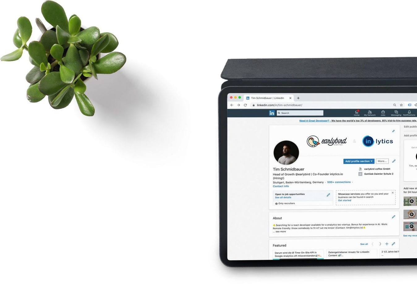 A LinkedIn page displayed on a tablet on a white table with a plant on it